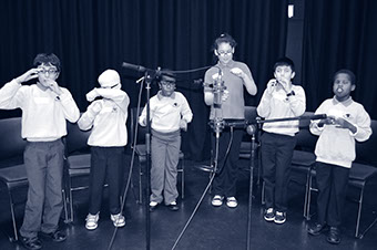 Children involved in an inclusive performing arts workshop, singing in front of microphones and signing.
