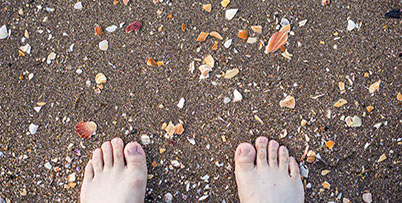 Image of bare feet standing in the sand surrounded by sharp pieces of shell.